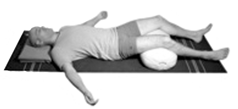 Supine relaxation pose with supports to relax the neck and low back.